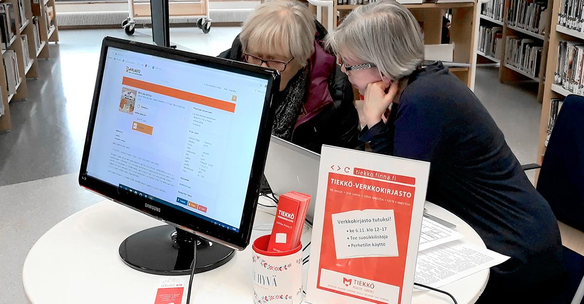 Kirjaston informaatikko neuvoo asiakasta verkkopalveluiden käytössä.