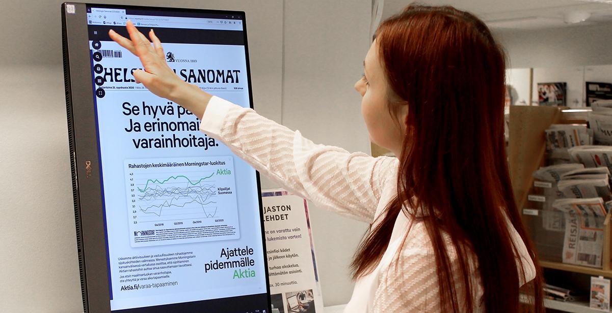 Nainen lukee lehteä e-lehtien lukukoneella