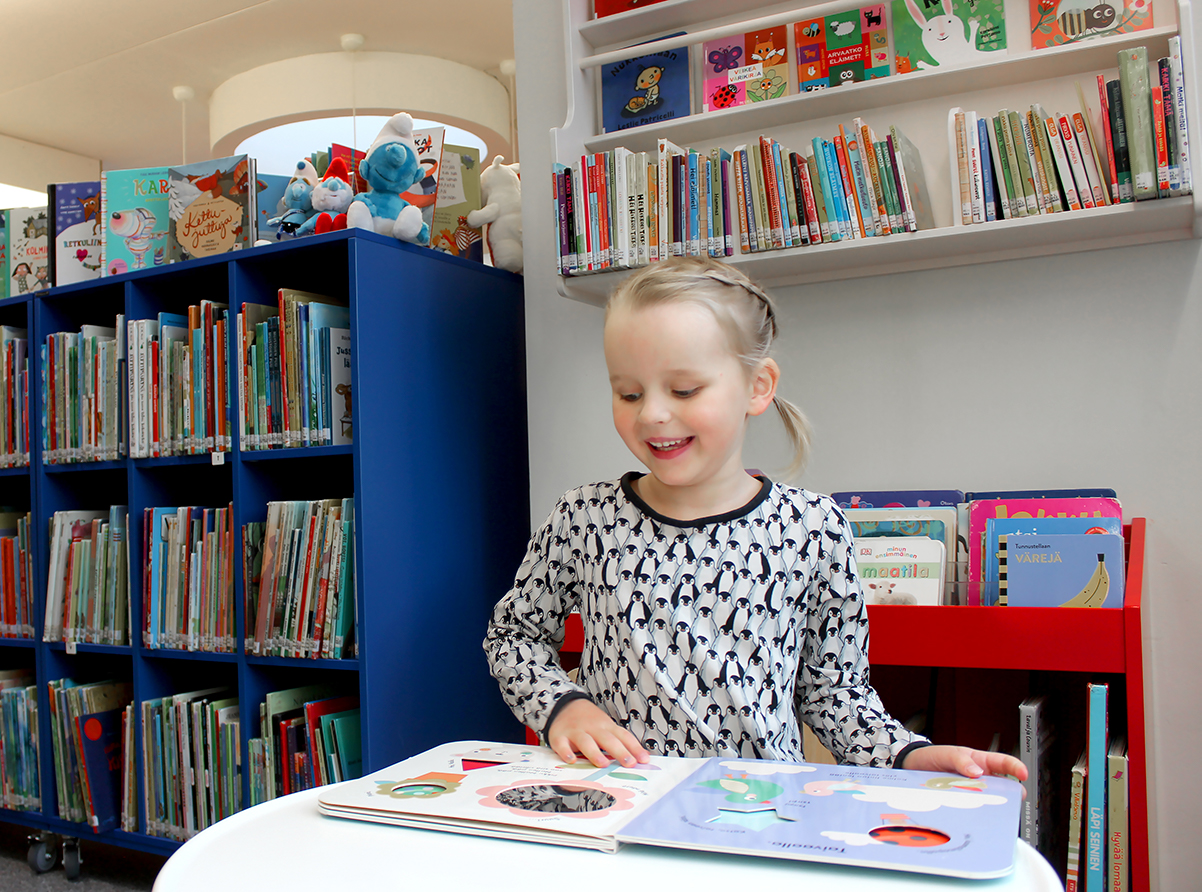 Lastenosastolla lapsi lukee kuvakirjaa