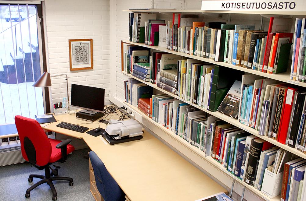 Kirjahyllyjä, työpiste ja tietokone
